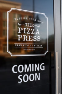 the pizza press coming soon written on a glass door